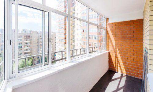 delle finestre in pvc di color bianco e un muro di mattoni a vista