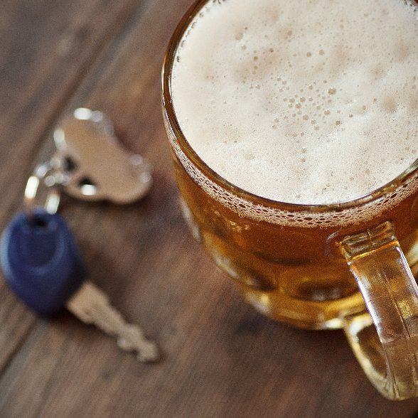 A set of keys rests next to a beer depicting the dangers of drinking and driving which usually results in a DUI defense lawyer