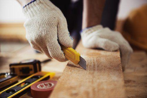 operaio con guanti da lavoro taglia un pezzo di legno con il cutter