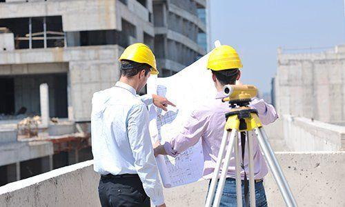 due operai che stanno guardando un progetto