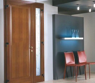 una porta di legno e accanto due sedie rosse e una mensola con due vasi in vetro