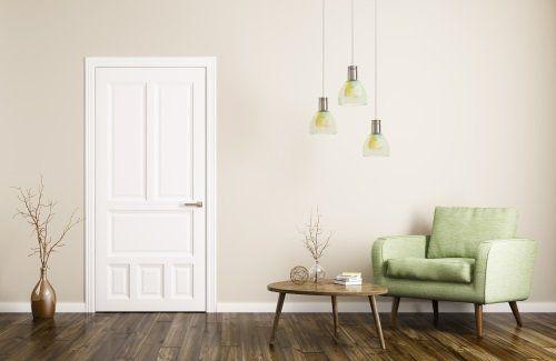 una porta bianca,un tavolino, un vaso e una poltrona verde