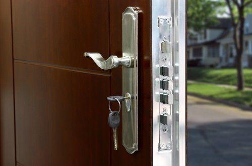 una porta blindata con vista della maniglia e di una chiave nella toppa