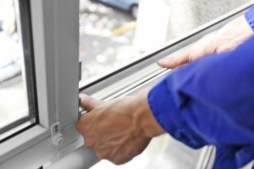 due mani che mettono una guarnizione a una finestra