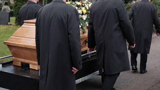 Un processo di sepoltura con una bara trasportata da uomini