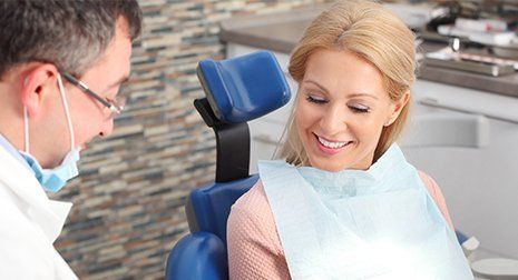 Woman sitting at dentist office and consulting with her male dentist in Malvern