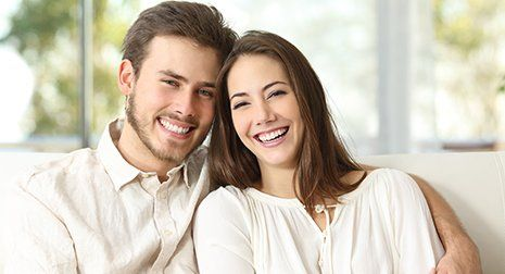 Young couple smiling with bright white teeth after dental cleaning in Malvern
