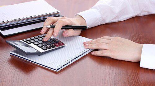 Usando la calcolatrice, carta e boligrafo