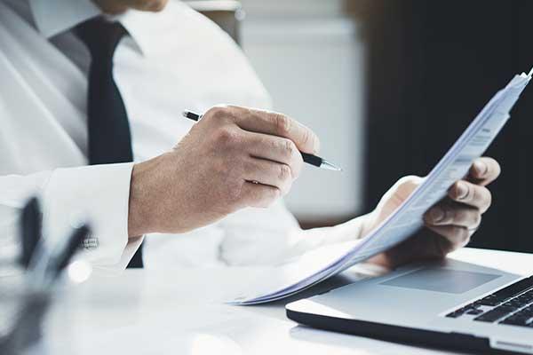 Un uomo alla scrivania esamina un documento tenendo una penna in mano