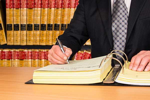 Un uomo seduto a una scrivania davanti una libreria scrive in un raccoglitore
