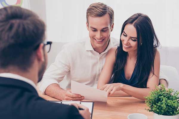 Una coppia sorridente seduta alla scrivania legge un foglio di fronte un consulente