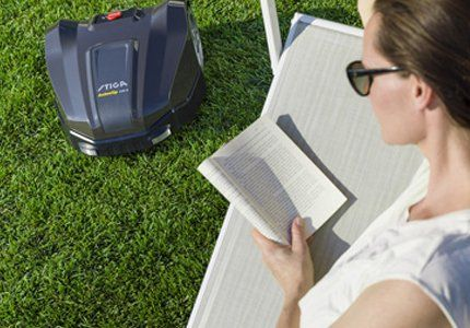 A lady sat reading in the sunshine of her garden while an Auto Mower moves around the lawn