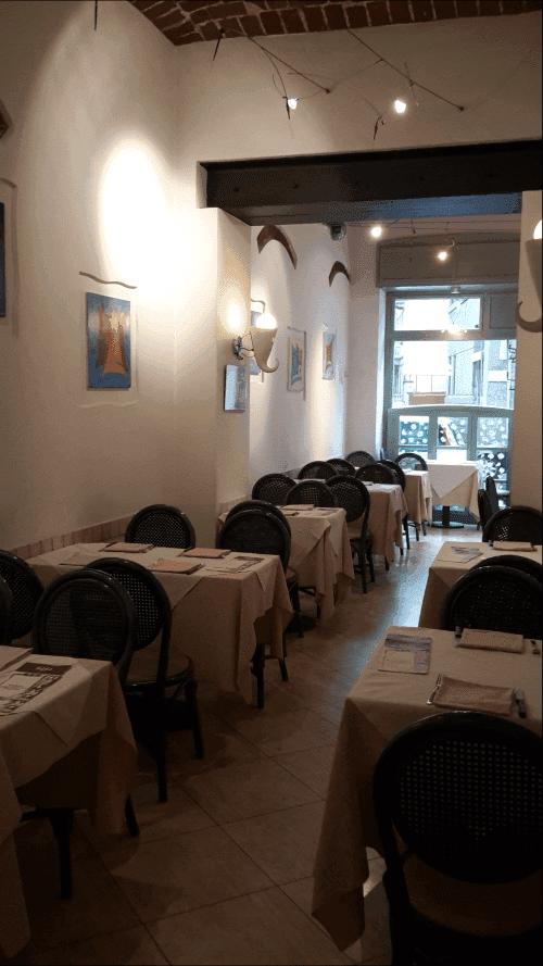 dei tavoli con sedie al interno di una pizzeria