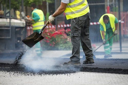 Worker pouring asphalt during road construction