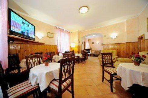sala con tavoli rotondi con tovaglie bianche, sedie di legno, due poltrone arancioni e sulla sinistra una tv a muro