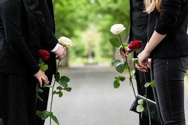 Quattro persone, quattro rose, due bianche, due rosse