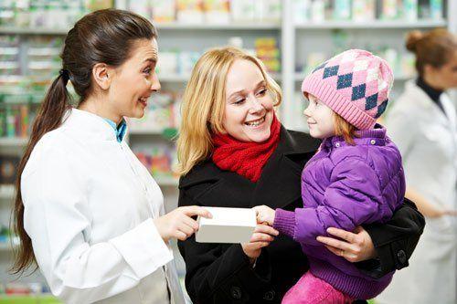 una donna con in braccio un bambino e accanto una farmacista sorridente con in mano un farmaco