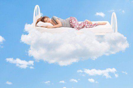 lettino con una ragazza che dorme il quale galleggia su di una nuvola