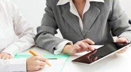 ragioniere che mostra un tablet al cliente, cliente che prende appunti, scrivania bianca