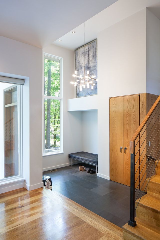 Modern residential architecture. The entry area was opened up to become a story and a half space. An oak closet enclosure carves into the tall wall.