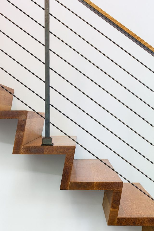 Modern residential architecture. The partially cantilevered stair becomes sculpture against the white wall.
