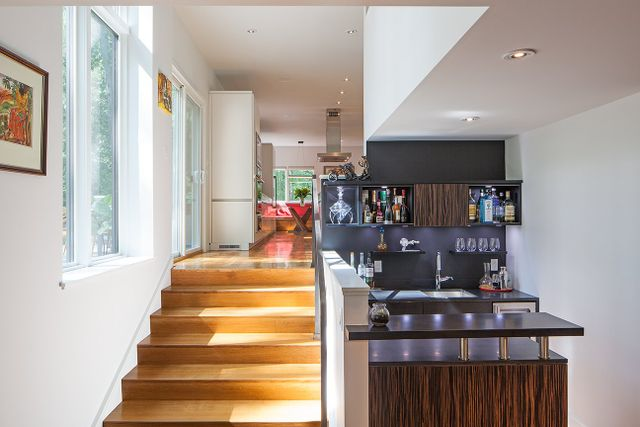 Modern residential architecture. A bar at the lower level dining and living room. New, wide stairs connecting to the kitchen level make a spacious connection not usually found in the typical split level arrangement.