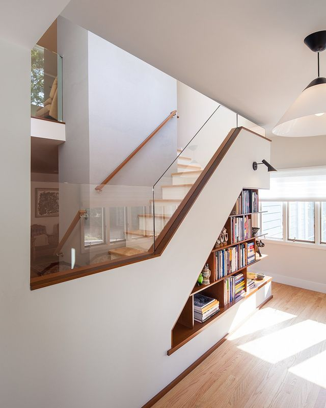 Modern residential architecture NJ. A wood bookcase makes use of the space under the stairs. AJ Wall Light. Opala Pendant. Glass Railing