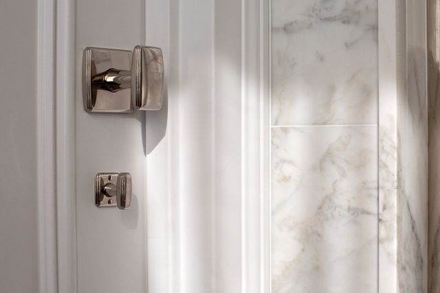 Modern residential architecture. Door Hardware. In the hall bath, the mosaic pattern was used on the floor in combination with statuary marble and white tiled walls.