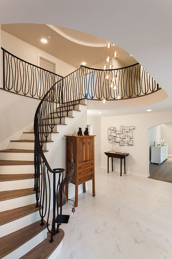 Modern residential architecture NJ. Curved ceiling elements were added to complement the existing stair. New wrought iron railings reflect the more contemporary design of the interior.