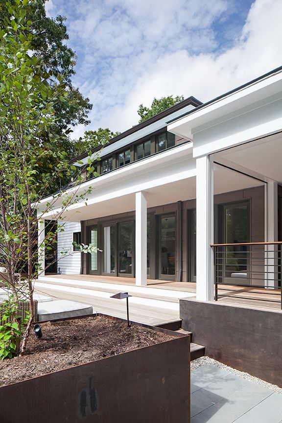 Modern residential architecture NJ. Coren steel planters frame the deck areas and complement the dark tone of the metal siding details used in the addition.