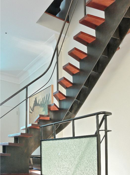 Modern residential architecture. Custom steel stair and railings with red stained oak treads added a modern insertion in a Manhattan townhouse. The glass guard was added during a second phase of renovations to this home.