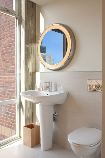 Modern residential architecture. Pedestal Sink from Toto, Grohe Faucet, Tech Lighting Tigris Round Mirror Light