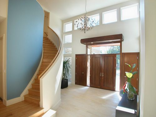 Modern residential architecture. This stair curves around the powder room enclosure and acts as a bold sculptural element in this large entry foyer.