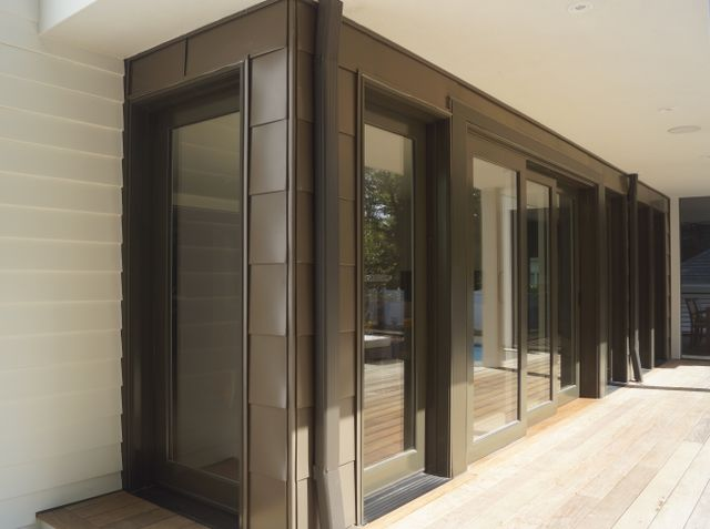 Modern residential architecture NJ. Metal siding matches the finish of the windows and sliding doors.