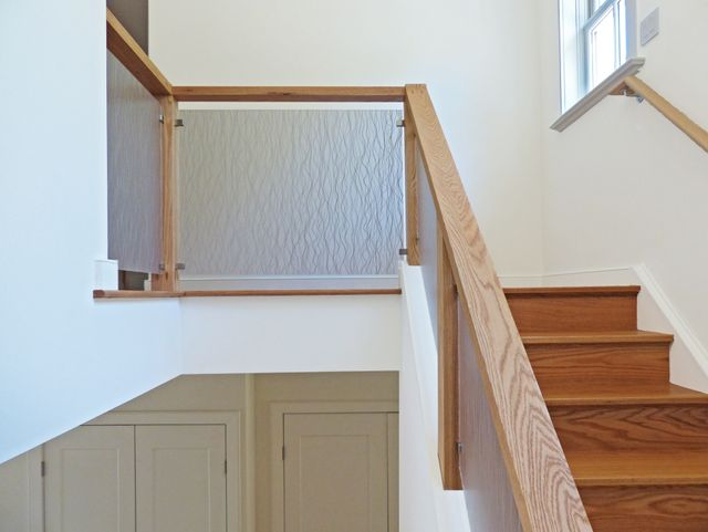 Modern residential architecture. Oak Railings with translucent resin infill panels provide interest to this simple stair structure