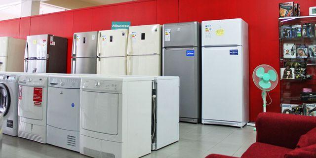 interno di un negozio con frigoriferi e lavatrici esposte, dietro un mobile rosso, sulla destra un ventilatore azzurro, uno scaffale con dei fon esposti in scatole e un divanetto rosso