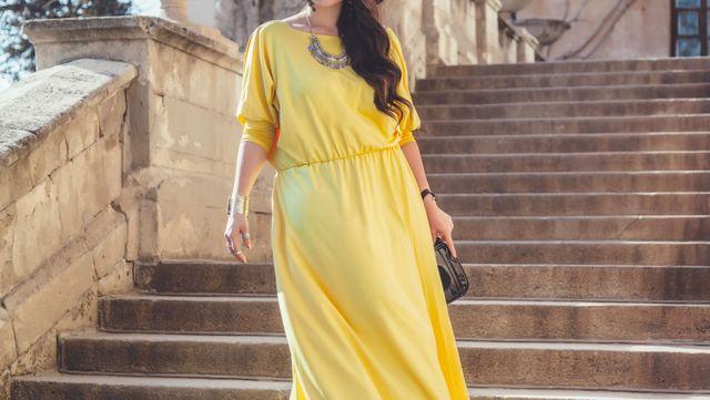 una donna con un abito lungo di color giallo