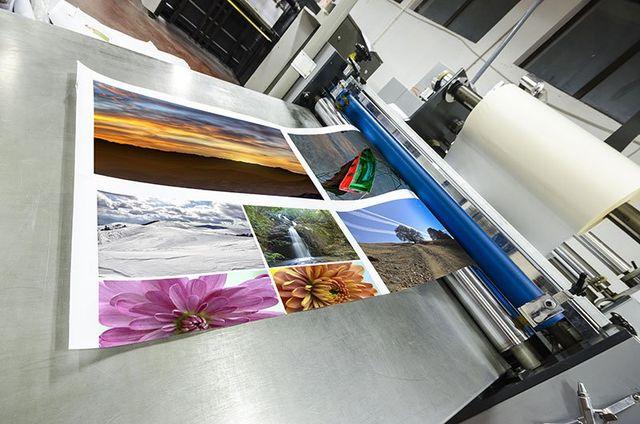 una stampante in una tipografia da cui fuoriescono dei fogli stampati raffiguranti delle immagini