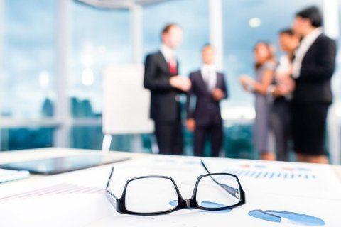 occhiali su un tavolo con sfondo sfuocato di persone in vestito elegante