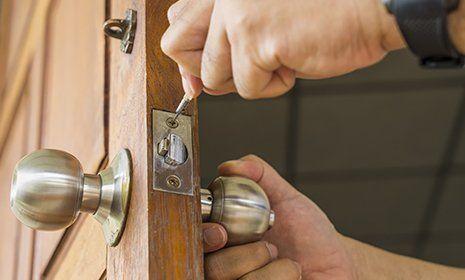 Due mani riparano la serratura di una porta