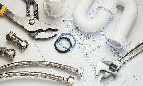 Attrezzi e articoli per l'idraulica poggiati su un progetto