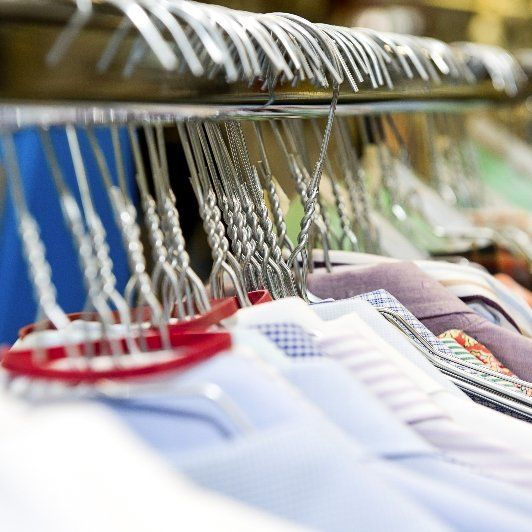 A line of dress shirts hanging on a rack