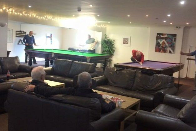 Men playing snooker and pool in the club house