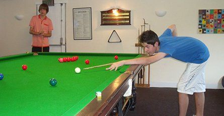 Two teenage boys playing pool