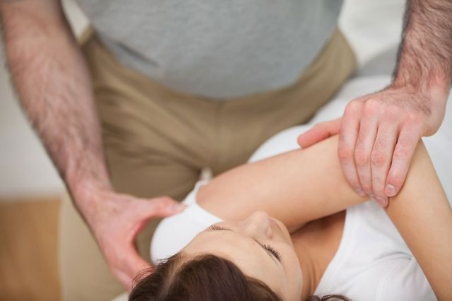 Fisioterapista ruotando ad una paziente nella barella