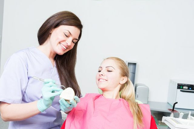 dentist and young lady smiling