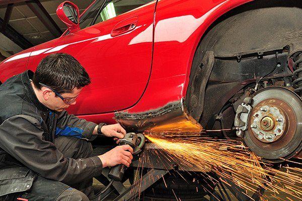 un uomo inginocchiato sta utilizzando un flessibile su una vettura di color rosso su un ponte elevatore con la parte della carrozzeria vicino alla ruota posteriore danneggiata