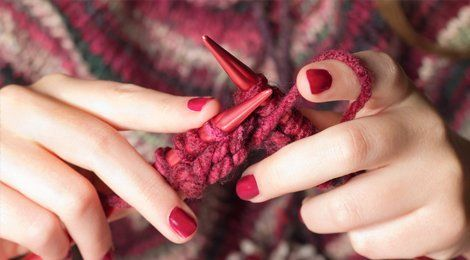 A red garment being knitted by a lady with red fingernails