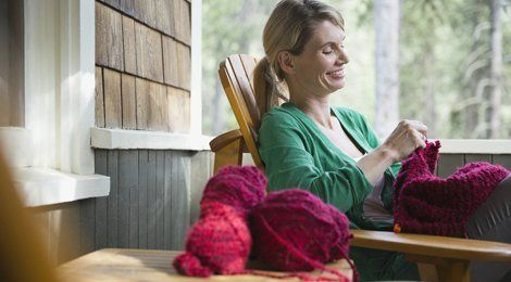 A lady relaxing by a window, knitting a purple garment