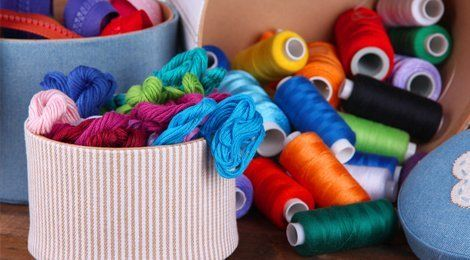Reels of coloured cotton around a striped container full of embroidery silks